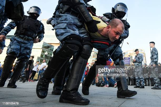 Riot police officers detain a protester during an unauthorised rally demanding independent and opposition candidates be allowed to run for office in...