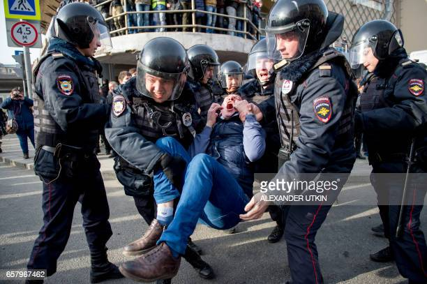 TOPSHOT Riot police officers detain a protester during an unauthorised anticorruption rally in central Moscow on March 26 2017 Thousands of Russians...