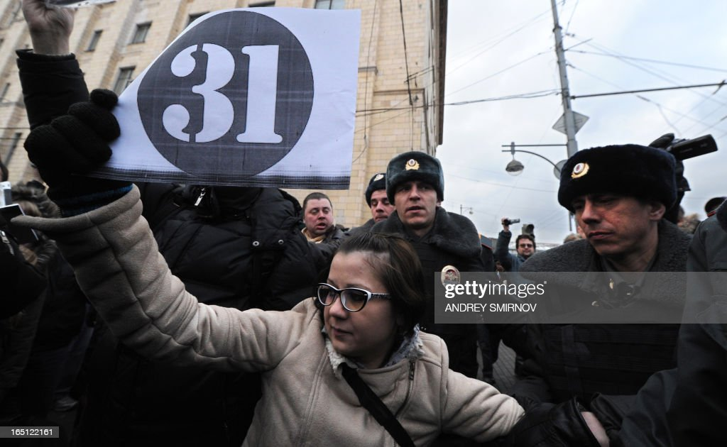 Riot police officers detain an opposition supporter in central Moscow on March 31, 2013 during an unauthorized rally by opposition activists to defend Article 31 of the Russian constitution which guarantees freedom of assembly. Russian opposition activists call on authorities to respect the right to organize rallies every 31st of the month, which often leads to arrests by police.