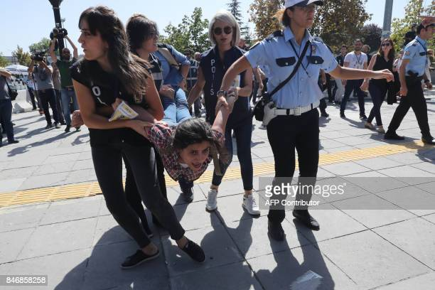 TOPSHOT Riot police officers detain protesters during the trial of two Turkish teachers who went on a hunger strike over their dismissal under a...