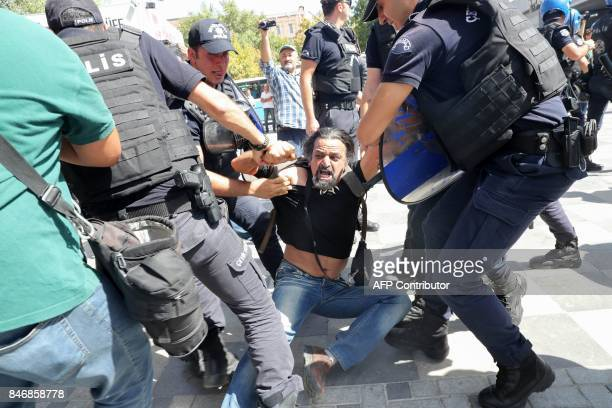 Riot police officers detain protesters during the trial of two Turkish teachers who went on a hunger strike over their dismissal under a government...
