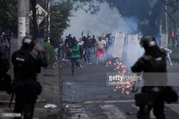 Riot police officers fire tear gas to demonstrators during clashes following a protest against a tax reform bill launched by President Ivan Duque, in...