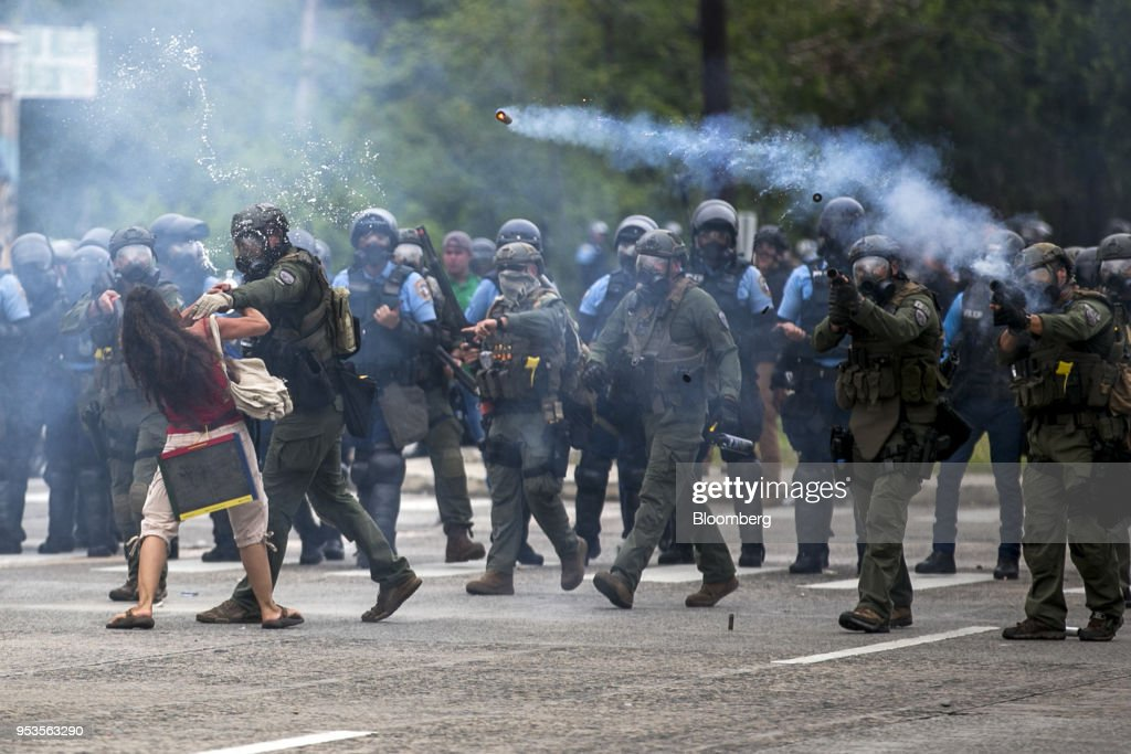 Riot police officers fire tear gas towards demonstrators during a protest against austerity measures in the Hato Rey neighborhood of San Juan, Puerto Rico, on Tuesday, May 1, 2018. Puerto Rico demonstrators battled police on San Juan's streets as they marched against proposed cuts to retirement benefits and looser labor laws as the bankrupt island seeks to reduce $74 billion of debt. Photographer: Xavier Garcia/Bloomberg via Getty Images