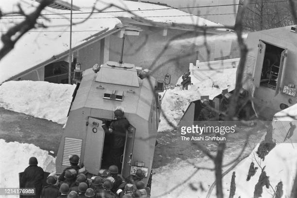 Riot police officers fire water cannon onto the Asama Sanso lodge where the United Red Army members take a hostage on February 24 1972 in Karuizawa...