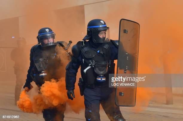 Riot police officers hold an orange flare during a nationwide protest day against the government's economic and social reforms on November 16 2017 in...