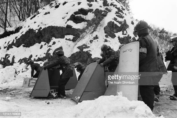 Riot Police officers holding shields approach to the Asama Sanso lodge as the United Red Army members take a hostage on February 23 1972 in Karuizawa...
