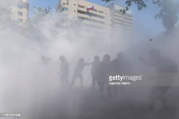 Riot police officers inside a cloud of tear gas during a national strike and general demonstration called by different workers unions on November 12,...