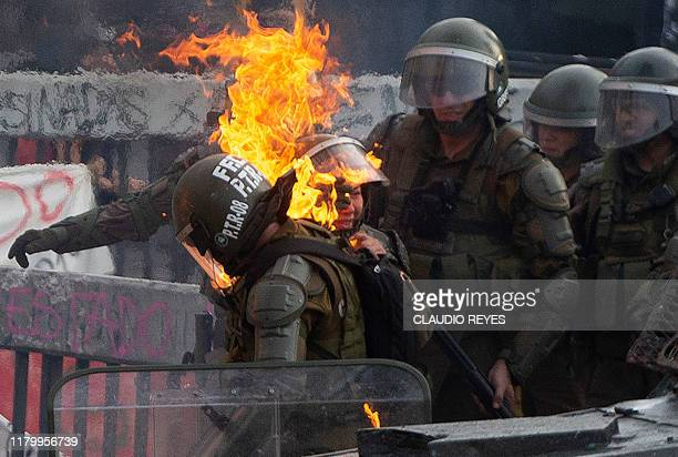 TOPSHOT A riot police officers is reached by a petrol bomb during clashes with demonstrators protesting against the economic policies of the...