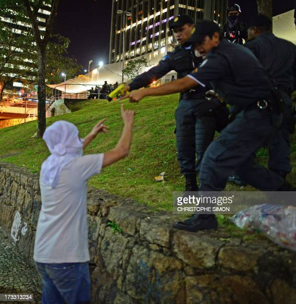 Riot police officers point at a demonstrator with a taser an electroshock weapon during clashes which erupted after a march by Brazilian workers in...