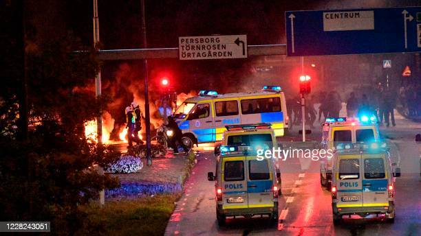 Riot police officers secure the area as smoke billows from burning tyres pallets and fireworks as a few hundred protesters riot in the Rosengard...