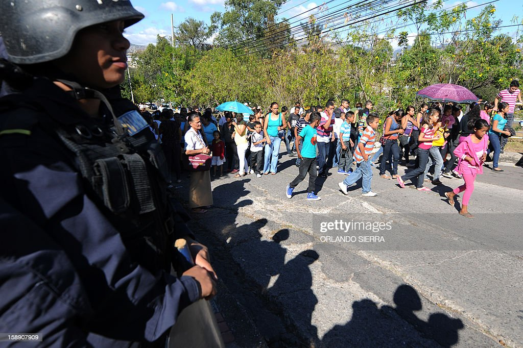 Riot police officers stand guard around the Supreme Court of Justice in Tegucigalpa, on January 3, 2013 as members of the National Confederation of Federations and Patrons of Honduras (Conafeph), some with their children, gather to demand the destitution of all the members of the Supreme Court. The head of Honduras' National Commission for Human Rights (CONADEH), Ramon Custodio, announced on Thursday he had asked the Inter-American Commission for Human Rights for preventive measures for the four judges who were removed by the Congress in December 2012 after they declared unconstitutional a purge plan at the police, deeply infiltrated by the organized crime. AFP PHOTO/Orlando SIERRA
