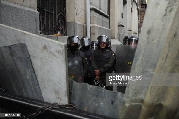Riot police officers stand guard as people from el Alto shout slogans asking the resignation of Interim President of Bolivia Jeanine Áñez during a...