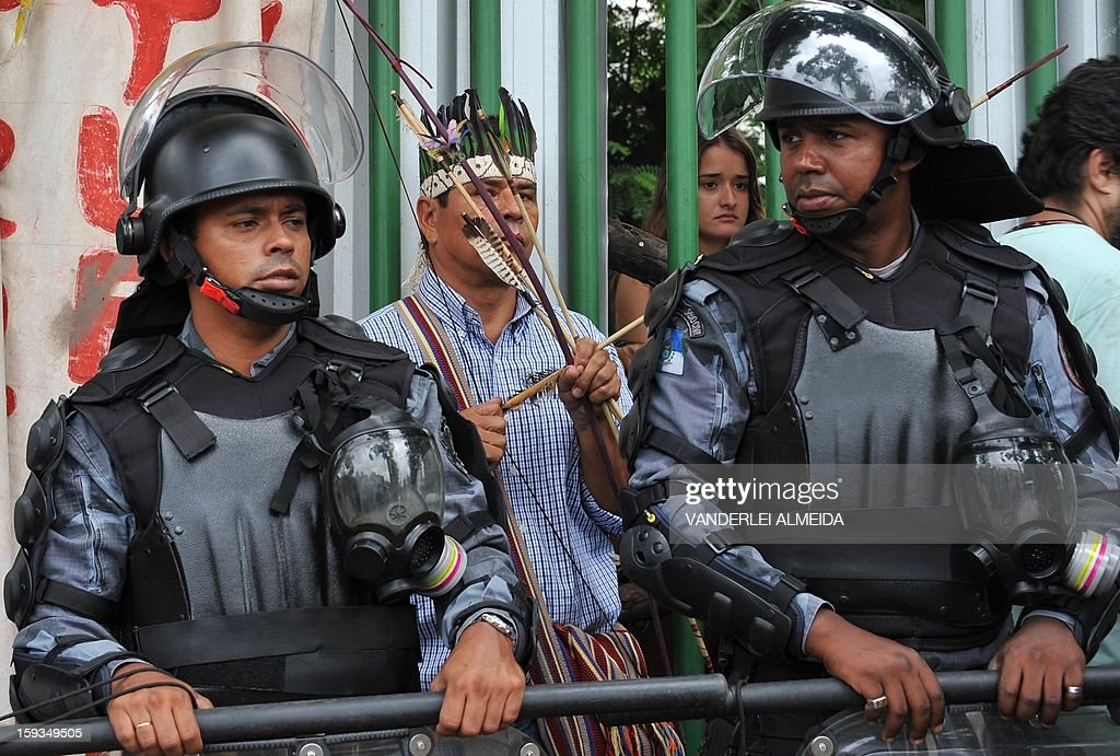 Riot Police officers stand guard at the entrance of the old indigenous museum --aka Aldea Maracana-- next to Maracana stadium in Rio de Janeiro on January 12, 2013. Indians have been occupying the place since 2006 as a protest against Rio de Janeiro's governmet decision to throw them out and pull down the building to construct 10,500 parking lots for the upcoming Brazil 2014 FIFA World Cup.