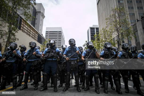 Riot police officers stand guard during a protest against austerity measures in the Hato Rey neighborhood of San Juan, Puerto Rico, on Tuesday, May...