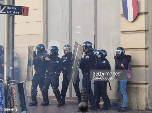 Riot police officers stand guard in front of a police headquarters during a demonstration of high school students protesting against French...