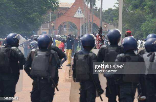 Riot police officers stand guard in front of demonstrators during a march called by the UAS union to call for better security measures against...