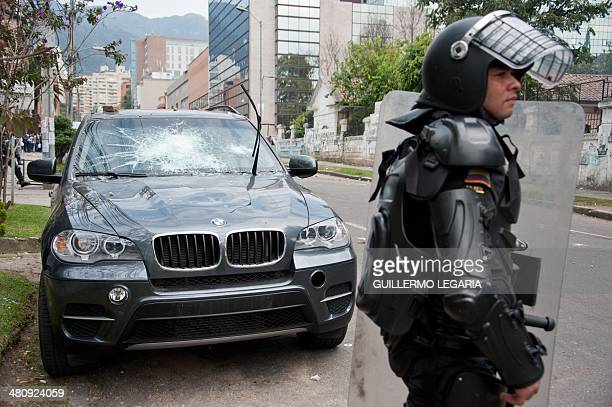 Riot police officers stand guard outside the headquarters of the Pedagogical University as students protest demanding government to improve the...