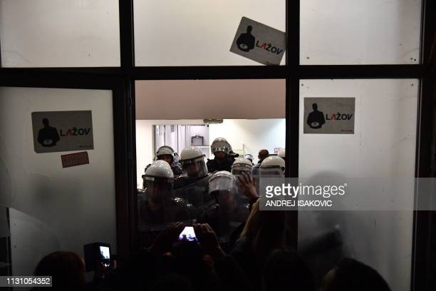 TOPSHOT Riot police officers stand guard to prevent protesters demonstrating against Serbian President to burst inside staterun TV headquarters at...