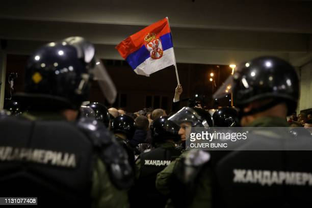 Riot police officers stand guard to prevent protesters demonstrating against Serbian President to burst inside staterun TV headquarters at the...
