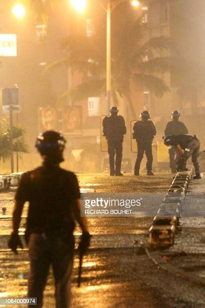 Riot police officers stand in a street at the Chaudron district during clashes with protesters overnight on November 20 2018 in SaintDenisdelaReunion...