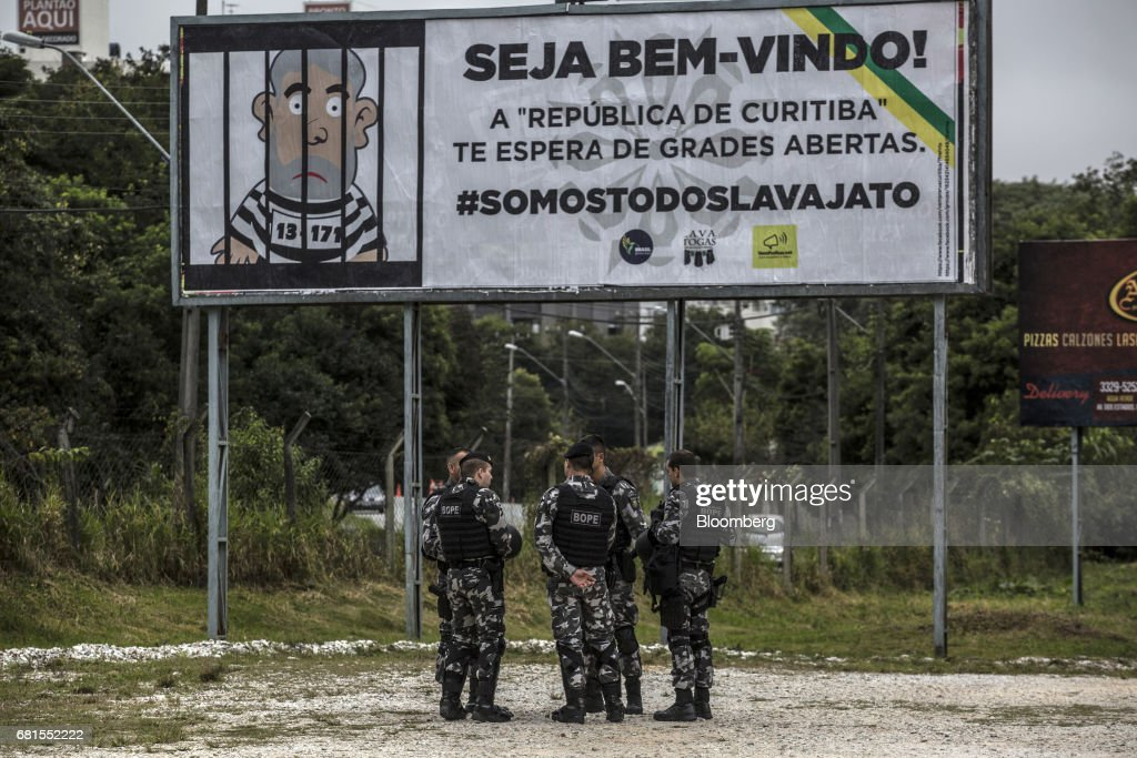 Riot police officers stand in front of a billboard depicting an illustration of Luiz Inacio Lula da Silva, former president of Brazil, and reads 'Welcome! The Republic of Curitiba awaits you with open bars' near the federal courthouse where Lula da Silva is scheduled to testify before Sergio Moro, the lead jurist in the sprawling corruption probe known as Operation Carwash, in Curitiba, Brazil, on Wednesday, May 10, 2017. Thousands of Brazilians are descending on the southern city of Curitiba before a showdown between one of the most popular leaders in the country's history and its most famous judge at a hearing that could determine the republic's future. Photographer: Dado Galdieri/Bloomberg via Getty Images