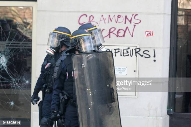 Riot police officers stand in front of a broken shop window and writings reading in French quotlets burn Macronquot during clashes on the sidelines...