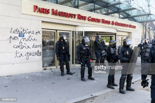 Riot police officers stand in front of a broken shop window and writings reading in French quotlegitimate or not our anger in your facequot during...