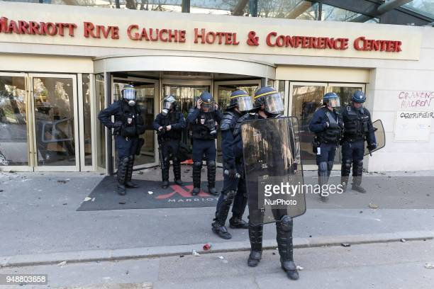 Riot police officers stand in front of a broken shop window during clashes on the sidelines of a demonstration on April 19 2018 in Paris as part of a...