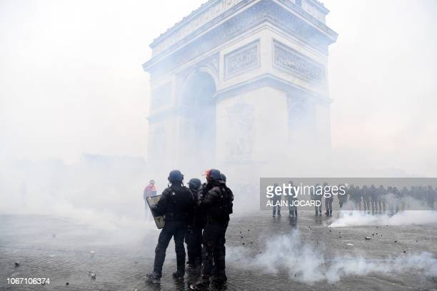 Riot police officers stand in position near the Arc of Triomphe during clashes with demonstrators during a protest of Yellow vests against rising oil...