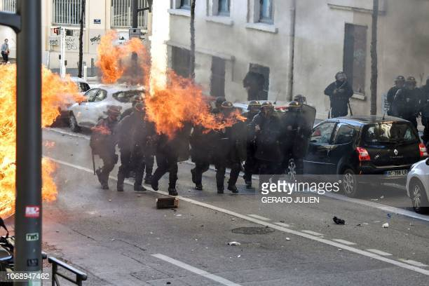 TOPSHOT Riot police officers stand in position next to a burning garbage on December 6 2018 in Marseille southern France on the sideline of a...