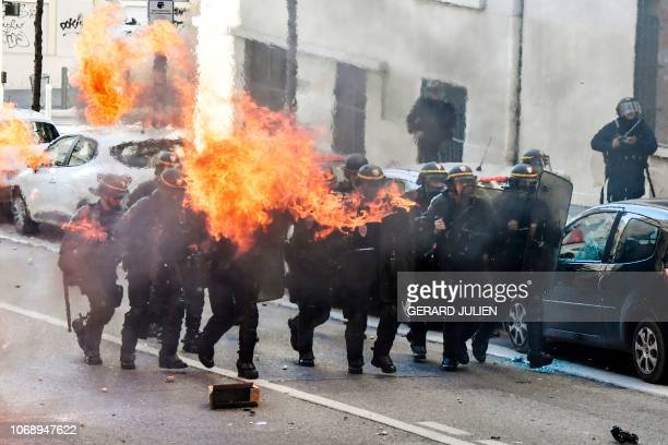 Riot police officers stand in position next to a burning garbage on December 6 2018 in Marseille southern France on the sideline of a demonstration...