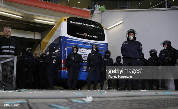 Riot police officers stand next to the team bus of Braunschweig during the Bundesliga Playoff first leg match between VfL Wolfsburg and Eintracht...