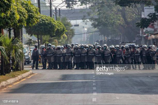 Riot police officers stand ready to arrest protesters and journalists during a demonstration against the junta military coup. Myanmar police fire...
