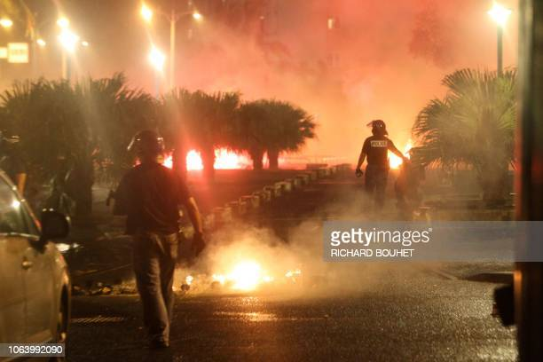 Riot police officers walk towards fires overnight on November 20 2018 at the Chaudron district in SaintDenisdelaReunion on the French overseas island...