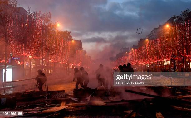 TOPSHOT Riot police officials walk through a cloud of teargas on the ChampsElysees in Paris on November 24 during a protest by yellow vests activists...