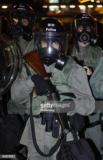 Riot police one with a tear gas cannister launcher poised move into position near the Convention Centre in Hong Kong Saturday December 17 2005 to...