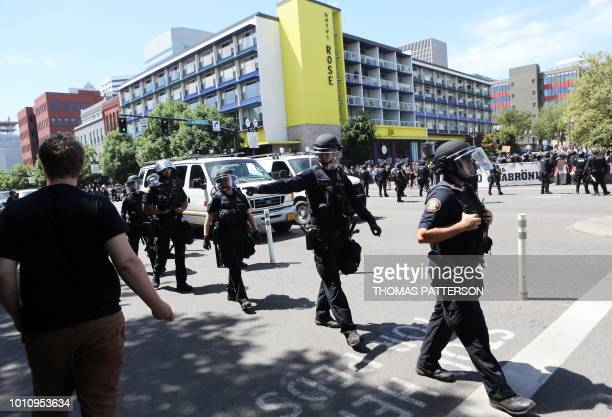 Riot police patrol the streets as altright activists antifascist protestors and people on all sides of the political spectrum gather for a campaign...
