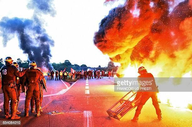TOPSHOT Riot police prepare to intervene to disperse refinery worker holding a blockade of the oil depot of DouchyLesMines to protest against the...
