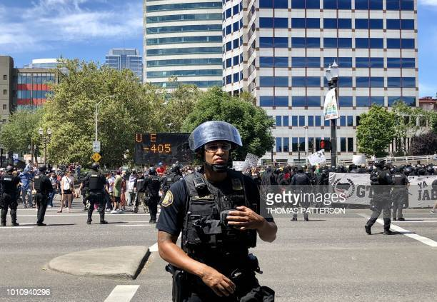 Riot police prevent opposing sides from crossing Naito Parkway August 4 2018 in downtown Portland Oregon Police in Portland braced for violence at...