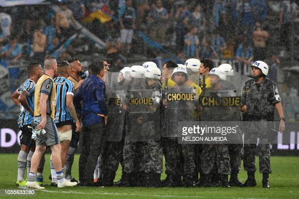 Riot police protect Uruguayan referee Andres Cunha as Brazil's Gremio footballers argue with him after losing their 2018 Copa Libertadores football...