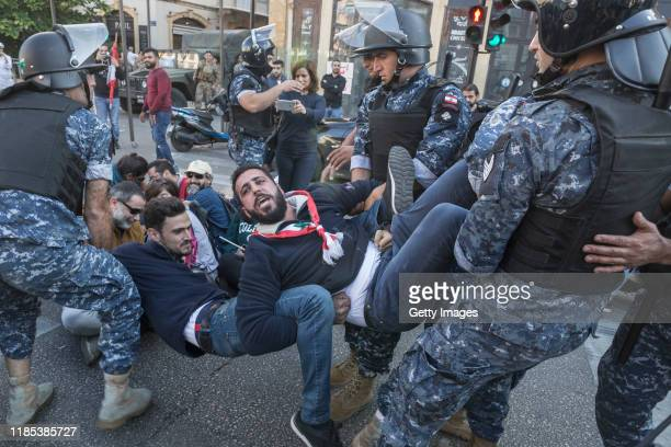 Riot police remove antigovernment protesters occupying an intersection on November 4 2019 in Beirut Lebanon Demonstrators cut roads around the...