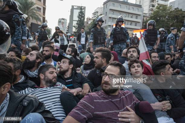 "Riot police remove anti-government protesters occupying the ""Ring"" intersection on November 4, 2019 in Beirut, Lebanon. Demonstrators cut roads..."