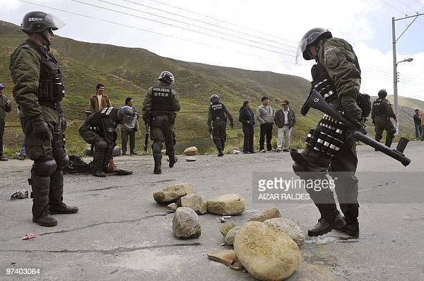 Riot police remove the stones placed by bus drivers who were blocking the provincial road during a 48hour national strike against a decree penalizing...