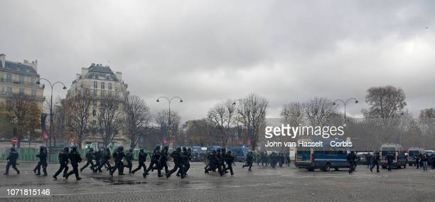 Riot police run during a protest against rising fuel prices on November 24 2018 in Paris France The police used tear gas and water cannon in an...