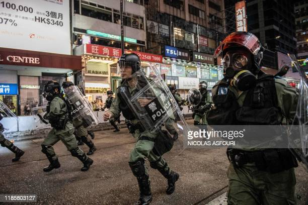 Riot police run towards protesters on Nathan road in Hong Kong on December 1, 2019. - Police fired tear gas and pepper spray in Hong Kong on December...