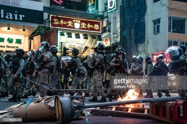 Riot police secure an area in front of a burning road block during a demonstration against the new national security law on July 1 2020 in Hong Kong...