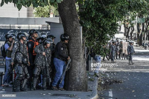 Riot police seen with their weapons taking cover behind a tree Demonstrators clashed with security forces during a protest at the Central University...