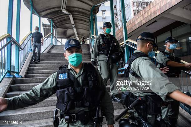Riot police set up a cordon near a group of pro-democracy protesters , who were stopped before being fined for breaking government-imposed social...