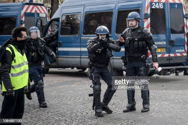 TOPSHOT Riot police shoots a nonlethal handheld weapon during a protest of Yellow vests against rising oil prices and living costs on the Champs...