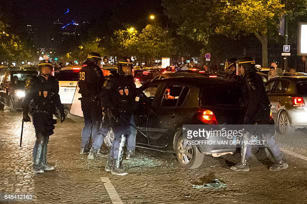 Riot Police smash a car after France won the Euro 2016 semifinal football match against Germany on the Champs Elysees in Paris on July 7 2016 France...